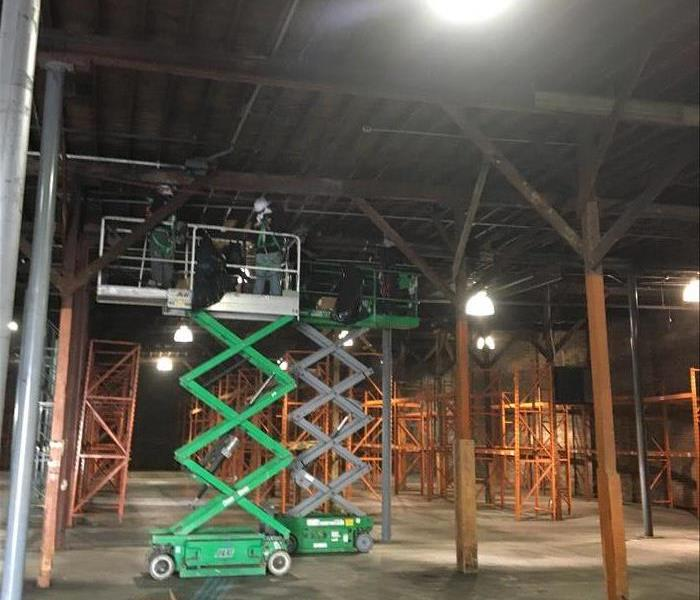 men on scaffolding in warehouse